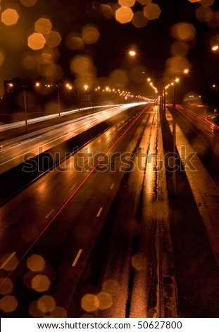 A night time shot of speeding traffic on a road