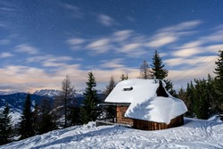 A night view of a little hut with snow on top and a dark blue night sky with stars in Wagrain, Salzuburg in Austria