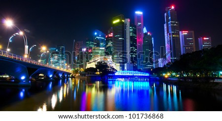 A night view of the city, with skyscrapers downtown and the bridge, which is reflected on the water surface (Singapore)