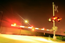 A night view of the gates at a railroad crossing. Lights a flashing and a blurred train is moving in the background.
