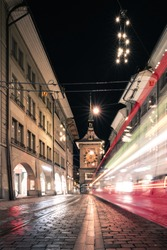 A nightshot of the oldtown, a bernmobil tram and the zytglogge tower of bern by night in winter, the capital of switzerland