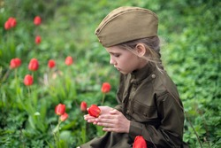 A nine-year-old beautiful girl with a long braid in a military uniform, in a military cap, sits in the grass and holds poppy flowers in her hands,around the poppies.Photo for the Victory Day on May 9
