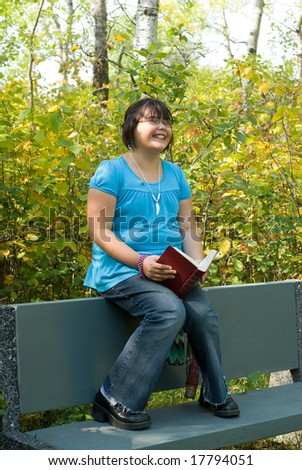 A nine year old girl reading a funny book outside