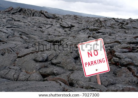 "A ""No Parking"" sign found in a dried up field of lava."