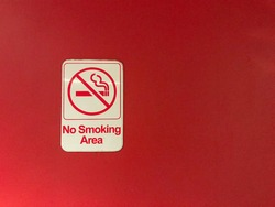 A no smoking sign on a red wall