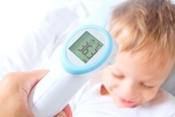A non-contact digital infrared thermometer recorded the normal body temperature of a child.The boy is recovering from an illness.Successful prevention of colds and flu in children concept.