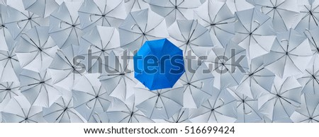A normal blue umbrella is different from the overturn grey umbrellas, Being different concepts, Business concept, Leader, Blue umbrella can protect rain, grey umbrellas can't protect rain, Top view.