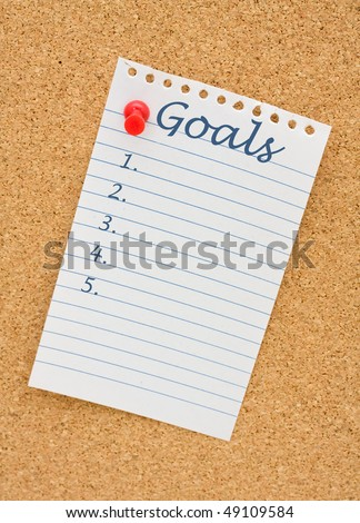 A note on white lined paper tacked to a corkboard, Making your goals