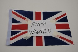 A note with the words, staff wanted, stuck with duct tape, over a flag of Great Britain. Labor shortage concept