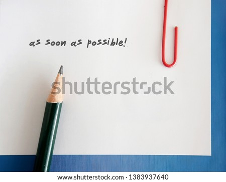 A note written AS SOON AS POSSIBLE clip with a blue notebook, with a pencil. Concept of urging someone to do the work,edit,read,approve the project urgently
