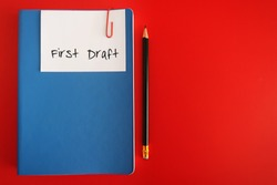 A note written FIRST DRAFT clip with a blue notebook, with a pencil, on red background. Concept of finishing first draft on book writing or business plan or creative project