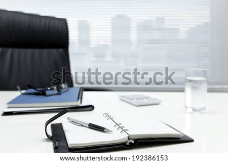 A notebook, pen and glass of water on an office desk.