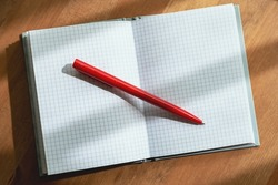 A notebook with a red ballpoint pen lie on a wooden table illuminated by the sun