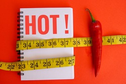 A notebook with a written text HOT, measuring tape and chilli on red background. Diet concept and scoville heat scale.