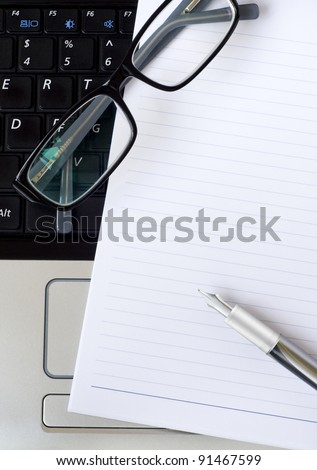 A notepad, pen and glasses on top of a laptop.