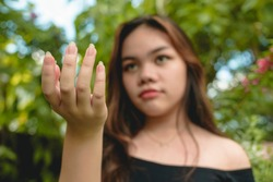 A noticeably irate woman extends her hand and demands for something. Camera focused on hand, face is slightly blurred.