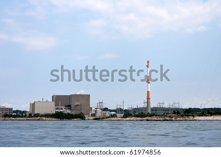 A nuclear power plant with large smoke stack and high power lines.