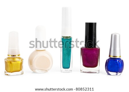 A number of different bottles with colored nail polish is isolated on a white background
