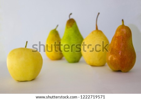 A number of dissimilar pears, different in color and shape. Near one round apple. Other, unlike. Variety of appearance. The background is blurred.