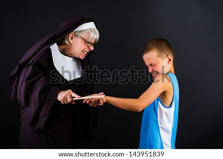 A nun hitting a boy on the knuckles with a ruler