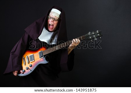 A nun jamming hard on an electric guitar