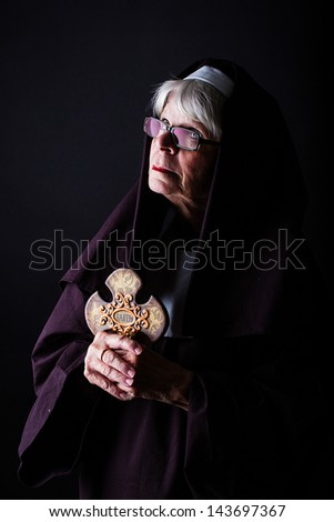 A nun looking up while holding a cross