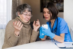 A nurse in a medical suit takes care and explains to an elderly patient how to use applications on a smartphone. Grandmother 80+ years old, does not understand how to communicate with a doctor online.