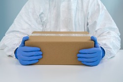 A nurse in a protective suit shows a box with both hands in a hospital. The healthcare worker receives medical supplies to fight Coronavirus Covid 19. Doctor wearing a PPE and gloves