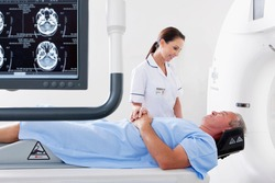 A nurse is comforting a patient laying on the city scan machine