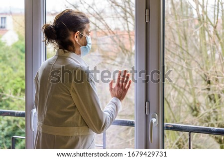 A nurse wearing a medical face mask and a white coat, is standing idle in front of a closed window, the hand on the glass, staring into space.