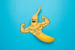 A nutritious banana with muscular arms. A hearty post-workout snack. Healthy food.