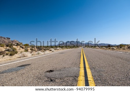 a obsolete asphaltic road with orange medial strip going threw a desert in the USA
