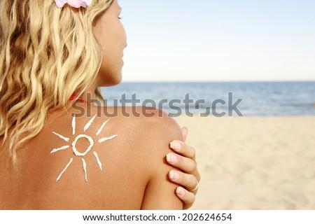 a of sun cream on the female back on the beach  #202624654