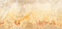 A old and cracked cement wall, with warm and ochre tones. pastel tones. large panoramic picture