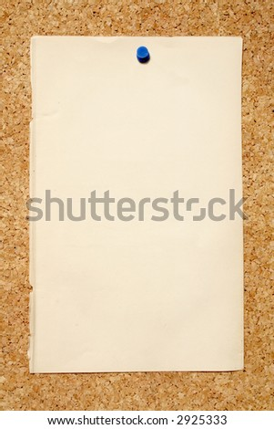 A old brown piece of paper pinned to a cork niticeboard. - stock photo