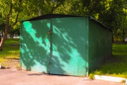 A old detached green metal double gate garage in the shade of trees. Old metal structure with peeling paint for car storage. Architectural facilities of the post-Soviet space.