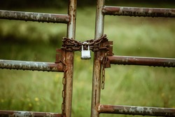 A old farm gate locked with rusty old chains around it- An old metal gate with a silver lock holding some chains on it- A locked gate