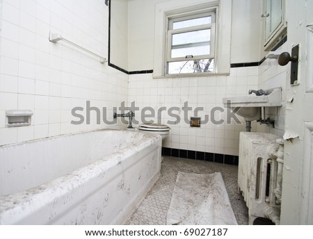 A old, filthy white bathroom in an abandoned house