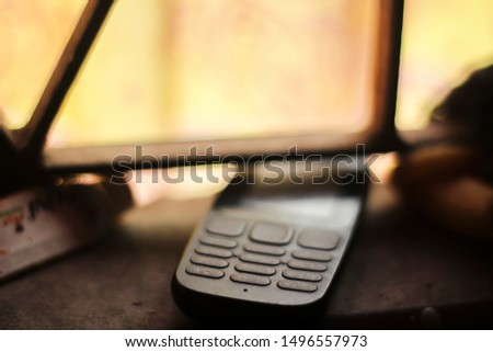 A old keypad system mobile phone against a blur background. #1496557973