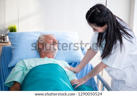 a old man or patient or elder sleeping on bed in hospital with doctor or nurse to take care and holding hands as health caring