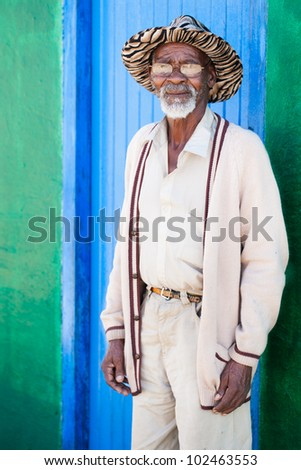A old man standing in front of his colorful shack