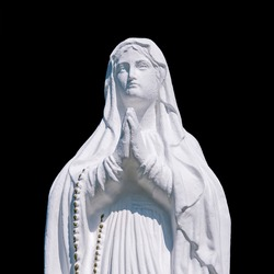 A old sculpture of  Virgin Mary. The stone statue is partially destroyed by time. Isolate on a black background (faith concept)