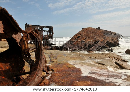 A once proud vessel lying in rusted pieces and is slowly disappearing Foto stock ©