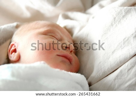 A one day old newborn baby is sleeping swaddled in white blankets in her hospital bed.