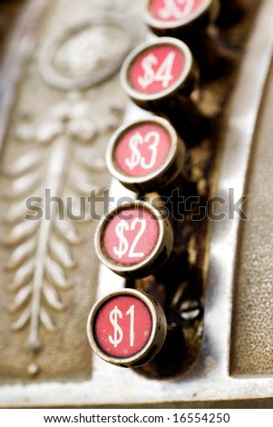 A one dollar button on a vintage cash register