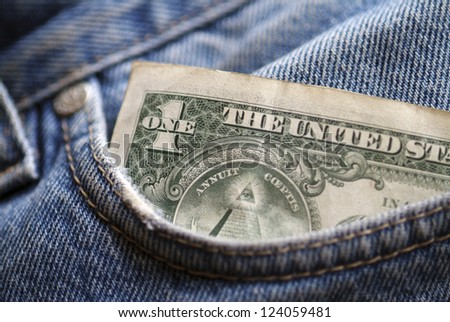 A one  dollar note in the pocket of denim trousers.