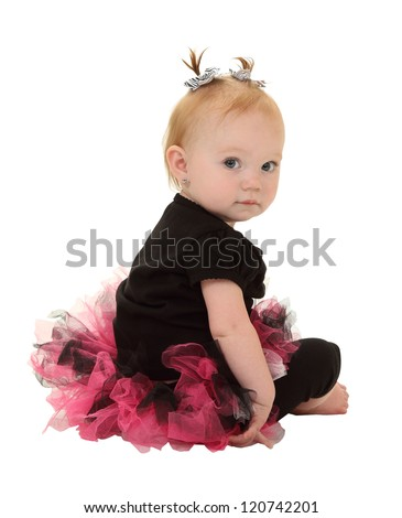A one year old girl in a tutu with pigtails takes a break from dancing isolated on white