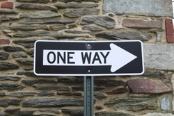 A oneway street sign against a stone wall.