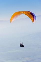 A orange Paraglider is flying in front of mountain