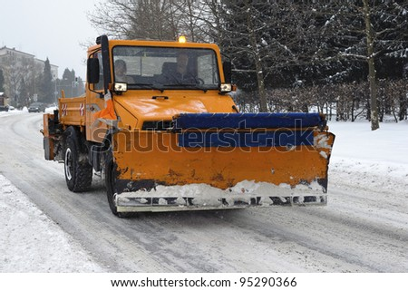 A orange snow plow truck ready for the storm